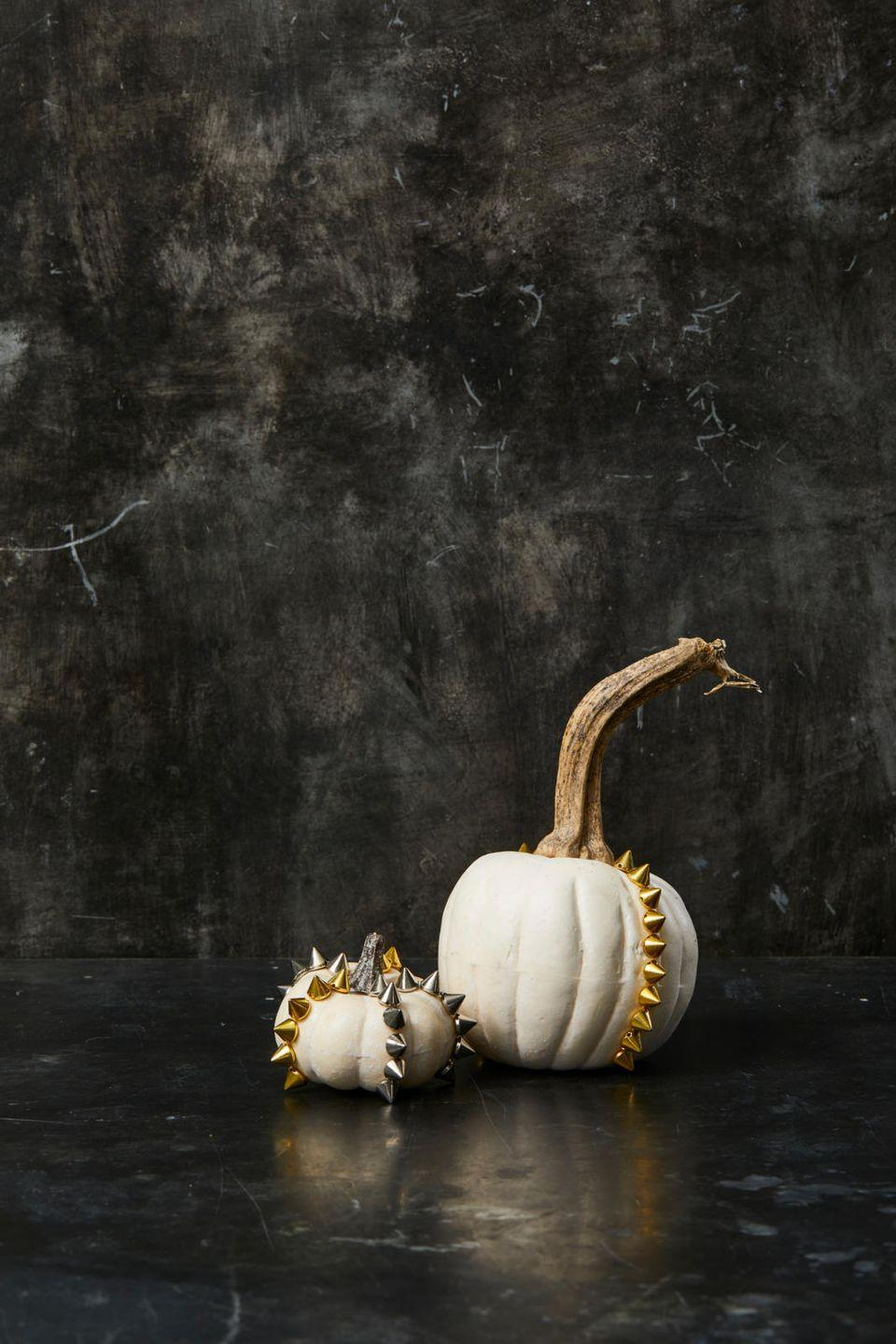 "<p>Mix up your holiday decorations with a little edge! Just paint each pumpkin one solid color and hot glue flat-bottomed studs in the pattern of your choice. </p><p><a class=""link rapid-noclick-resp"" href=""https://www.amazon.com/100pcs-Square-Leathercraft-Pyramid-Nailheads/dp/B07FLFCNZS/?tag=syn-yahoo-20&ascsubtag=%5Bartid%7C10055.g.1714%5Bsrc%7Cyahoo-us"" rel=""nofollow noopener"" target=""_blank"" data-ylk=""slk:SHOP FLAT-BOTTOMED STUDS"">SHOP FLAT-BOTTOMED STUDS </a></p><p><strong>RELATED: </strong><a href=""https://www.goodhousekeeping.com/holidays/halloween-ideas/g1566/easy-halloween-craft-ideas/"" rel=""nofollow noopener"" target=""_blank"" data-ylk=""slk:60 Easy Halloween Crafts for Adults Who Love All Things Spooky and Spidery"" class=""link rapid-noclick-resp"">60 Easy Halloween Crafts for Adults Who Love All Things Spooky and Spidery</a></p>"