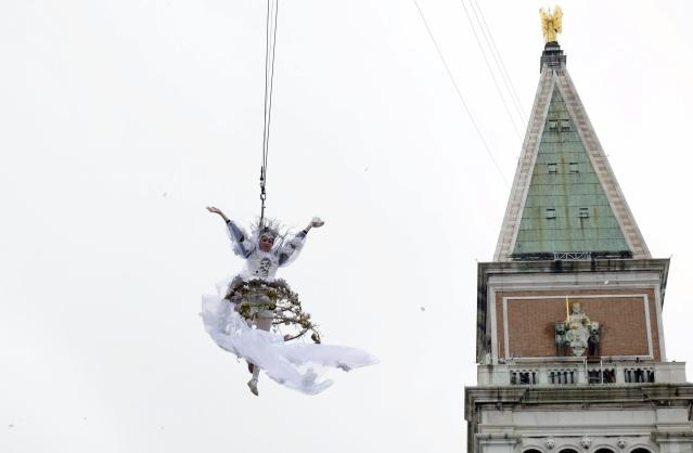 Sochi 2014 Winter Olympic games bronze medallist Italy's Carolina Kostner performs at the traditional Columbine descends from Saint Mark's bell tower on an iron cable during the Venetian Carnival in Venice, March 2, 2014. REUTERS/Manuel Silvestri (ITALY - Tags: SPORT SOCIETY)