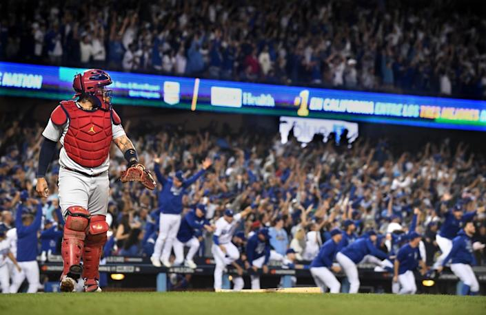 St. Louis Cardinals catcher Yadier Molina walks off the field as the Los Angeles Dodgers celebrate a walk-off home run