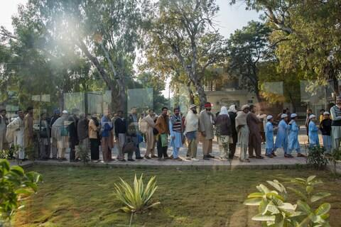 Workers stand in line outside a free communal kitchen at lunch time - Credit: Saiyna Bashir