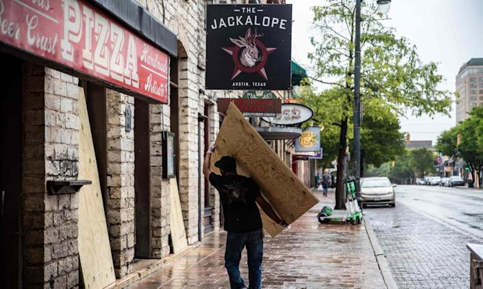 A worker carries a piece of plywood in Austin, Texas Friday after the governor ordered bars to close.