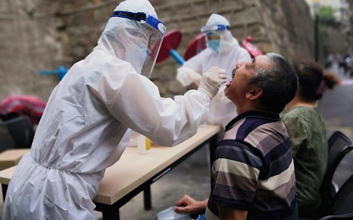 A medical worker swabs the throat of a citizen for a nucleic acid testing during the COVID-19 epidemic on July 19, 2020 in Urumqi - China News Service/China News Service