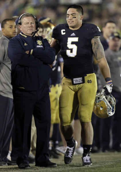 FILE - In this Nov. 17, 2012, file photo, Notre Dame linebacker Manti Te'o, right, pats coach Brian Kelly on the back after Te'o left the game during the second half of an NCAA college football game in South Bend, Ind. Kelly, talking to the media for the first time since the BCS title game, is expected to talk about his interview with the Philadelphia Eagles and the Te'o situation during a teleconference Tuesday. (AP Photo/Michael Conroy, File)