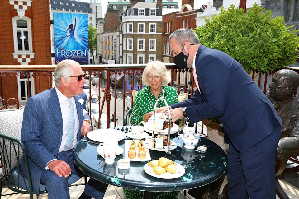 Britain's Prince Charles and Camilla, Duchess of Cornwall, enjoy afternoon tea on the terrace beside a life-sized statue of a playwright Noel Coward during a visit to Theatre Royal in London, Britain June 23, 2021. Tim P. Whitby/Pool via REUTERS