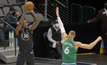 New York Knicks forward Julius Randle (30) attempts a 3-point shot against Dallas Mavericks center Kristaps Porzingis (6) during the first half of an NBA basketball game Friday, April 16, 2021, in Dallas. (AP Photo/Ron Jenkins)