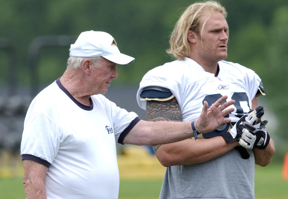 FILE - In this July 25, 2003, file photo, St. Louis Rams offensive line coach Jim Hanifan, left, works with Kyle Turley during NFL football training camp in Macomb, Ill. Hanifan, the former St. Louis Cardinals coach who returned to the city as offensive line coach to help the Rams win the Super Bowl, has died. He was 87. Hanifan's daughter, Kathy Hinder, told the St. Louis Post-Dispatch that he died Tuesday, Nov. 23, 2020. She said the cause of death hasn't been determined, but said it wasn't related to COVID-19. (AP Photo/James A. Finley, File)
