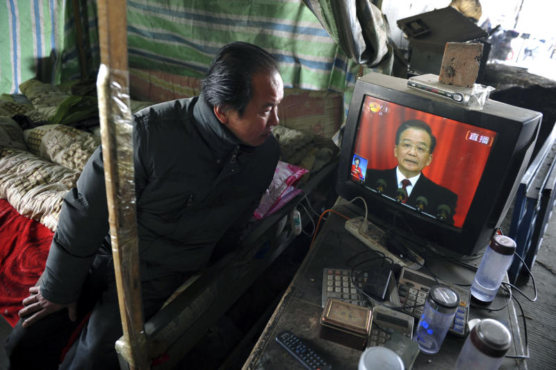 A vendor watches the live telecast of the annual government work report by outgoing Premier Wen Jiabao on a television in a vegetable wholesale market in Fuyang in central China's Anhui province Tuesday, March 5, 2013. China's government promised its people Tuesday deficit-fueled spending to fight deep-seated corruption, improve the despoiled environment and address other quality-of-life issues demanded by an increasingly vocal public looking for change.  (AP Photo) CHINA OUT