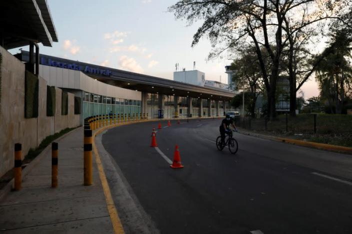 A policeman rides a bicycle after El Salvador's President Bukele ordered the closing of the airport in San Luis Talpa