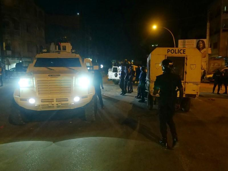 Police vehicles are parked at the scene during protests over a nationwide dusk-to-dawn curfew imposed because of the coronavirus disease (COVID-19) in Dakar