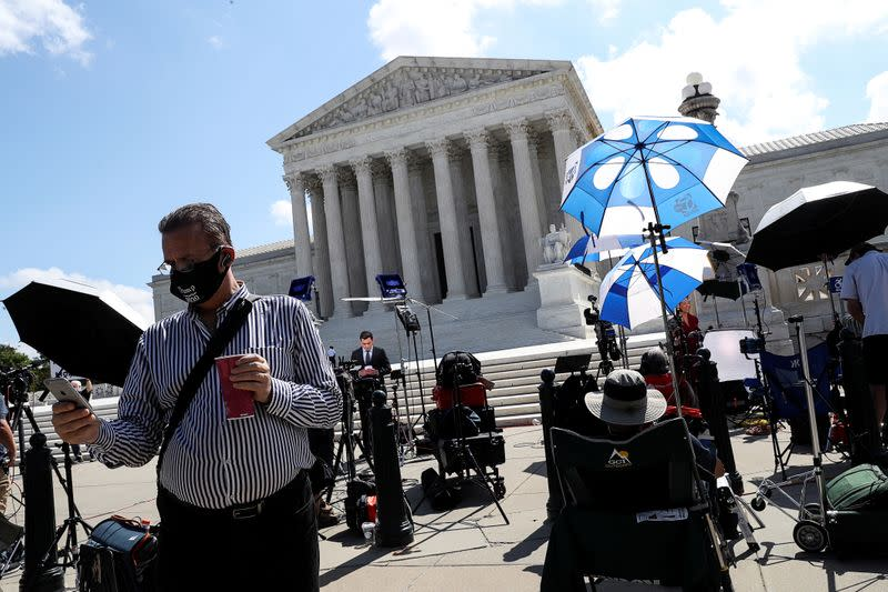 Members of news media gather outside the U.S. Supreme Court in Washington