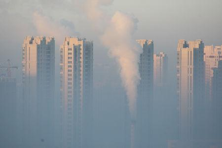 A chimney is seen in front of residential buildings during a polluted day in Harbin