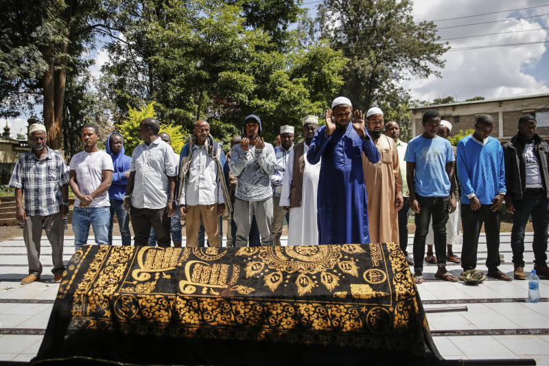 """Relatives and friends pray over the body of 13-year-old Yasin Hussein Moyo at his burial, at the Kariakor cemetery in Nairobi, Kenya Tuesday, March 31, 2020. The family of a 13-year-old boy is in mourning after police in Kenya's capital are accused of shooting him dead while enforcing a coronavirus curfew. Kenya's police inspector general has ordered an investigation into the boy's death by """"stray bullet,"""" including a forensic analysis of all firearms held by officers at the scene. (AP Photo/Brian Inganga)"""