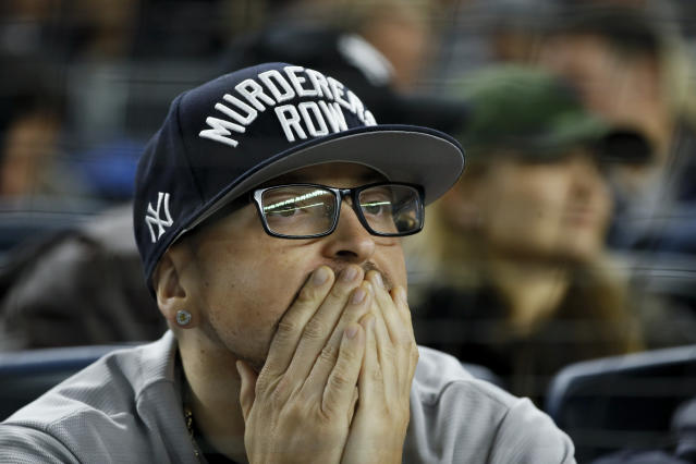 A fan watches during the fifth inning in Game 4 of baseball's American League Championship Series between the Houston Astros and the New York Yankees Thursday, Oct. 17, 2019, in New York. (AP Photo/Matt Slocum)