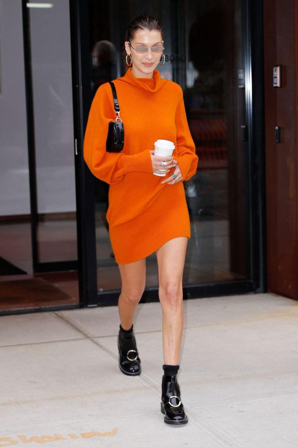 """<p>In an orange turtleneck sweater dress, <a href=""""https://www.luvaj.com/products/amalfi-tube-hoops-gold"""" rel=""""nofollow noopener"""" target=""""_blank"""" data-ylk=""""slk:Luv Aj"""" class=""""link rapid-noclick-resp"""">Luv Aj</a> hoop earrings, retro shades, black patent leather boots and <a href=""""https://www.net-a-porter.com/us/en/product/1086339/by_far/rachel-patent-leather-shoulder-bag"""" rel=""""nofollow noopener"""" target=""""_blank"""" data-ylk=""""slk:By Far"""" class=""""link rapid-noclick-resp"""">By Far</a> purse out in NYC.</p>"""