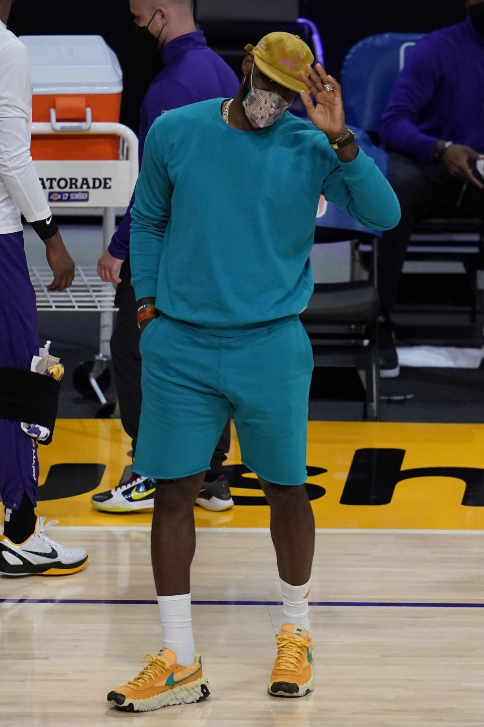 Los Angeles Lakers forward LeBron James (23) waves to a person across the court during the second quarter of a basketball game against the New York Knicks Tuesday, May 11, 2021, in Los Angeles. James did not play. (AP Photo/Ashley Landis)