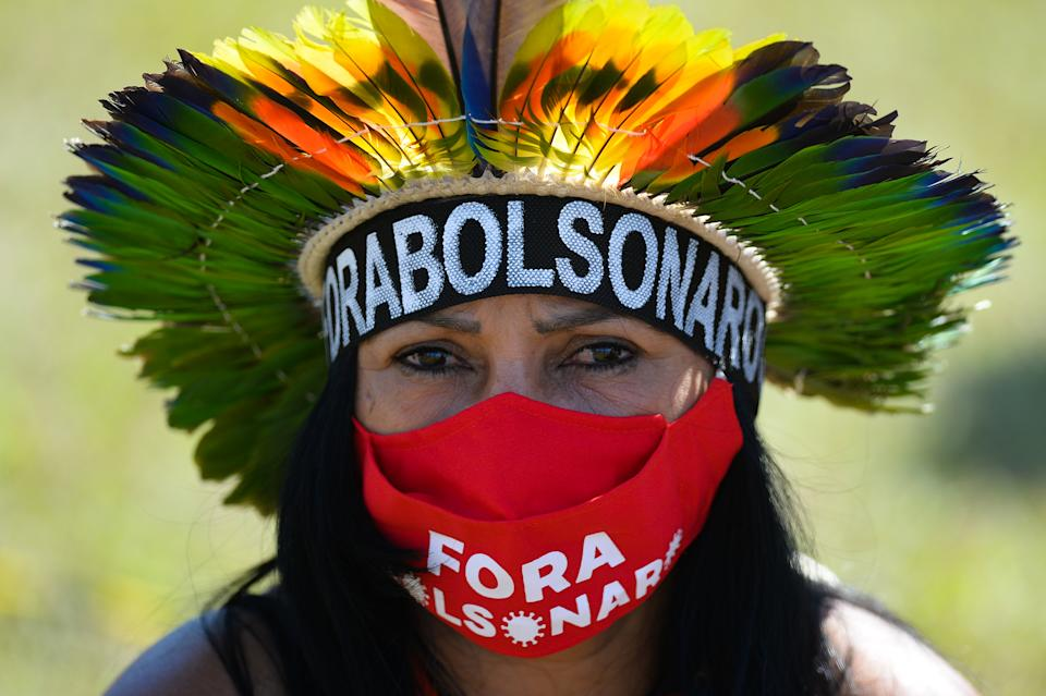 BRASILIA, BRAZIL - JUNE 19: A member of an indigenous community wears a face mask that reads 'Bolsonaro out' during a protest against Bolsonaro's administration on June 19, 2021 in Brasilia, Brazil. Brazilian president Jair Bolsonaro is facing a probe  for pandemic mismanagement as the country approaches the half million deaths from COVID. The controversial decision to host the Copa America 2021 amid the coronavirus crisis is questioned by a large part of the population. (Photo by Andressa Anholete/Getty Images)