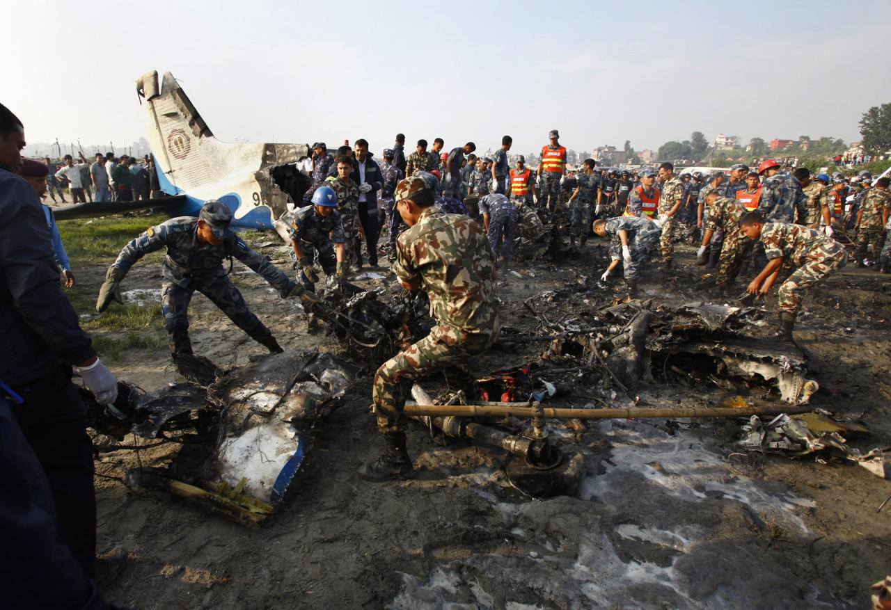 Nepalese police salvage debris at the crash site of a Sita Air airplane near Katmandu, Nepal, early Friday, Sept. 28, 2012. The plane carrying trekkers into the Everest region crashed just after takeoff Friday morning in Nepal's capital, killing all 19 people on board, authorities said. (AP Photo/Niranjan Shrestha)