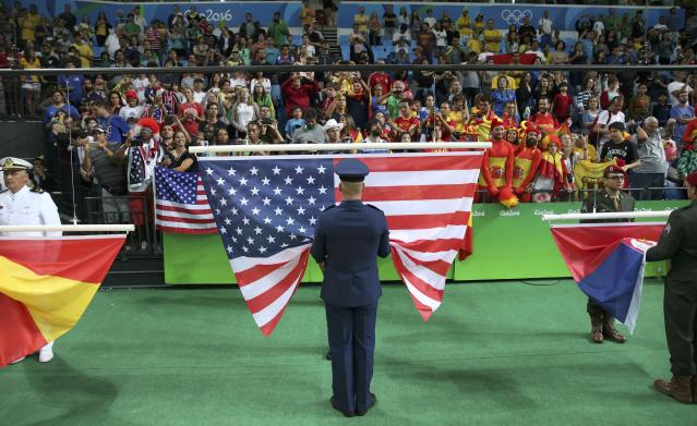 2016 Rio Olympics - Basketball - Final - Women's Gold Medal Game USA v Spain - Carioca Arena 1 - Rio de Janeiro, Brazil - 20/8/2016. The U.S. flag is prepared to be hoisted along with those of Spain (L) and Serbia (R) during the medal presentation ceremony for the women's basketball top finishers. REUTERS/Shannon Stapleton FOR EDITORIAL USE ONLY. NOT FOR SALE FOR MARKETING OR ADVERTISING CAMPAIGNS.