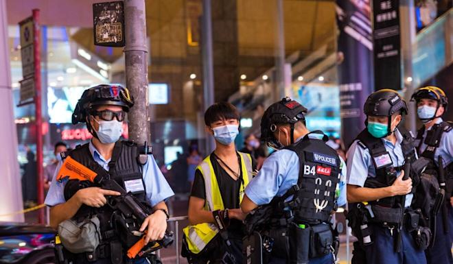 A student journalist is stopped and searched by riot police in Mong Kok in August. Photo: Getty Images