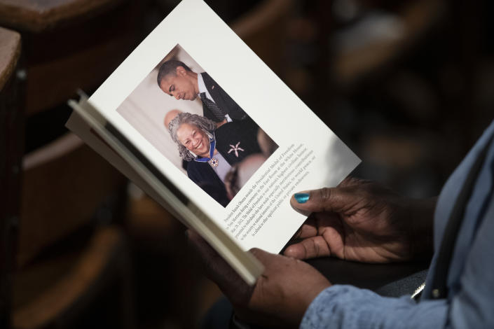 A person looks through the program before the start of the Celebration of the Life of Toni Morrison, Thursday, Nov. 21, 2019, at the Cathedral of St. John the Divine in New York. (AP Photo/Mary Altaffer)