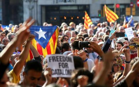 A crowd of protesters gather outside the Catalan region's economy ministry after junior economy minister Josep Maria Jove was arrested - Credit: REUTERS
