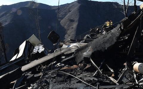 <span>Firefighters stand beside a burnt out home after the Skirball wildfire swept through the exclusive enclave of Bel Air</span> <span>Credit: AFP </span>