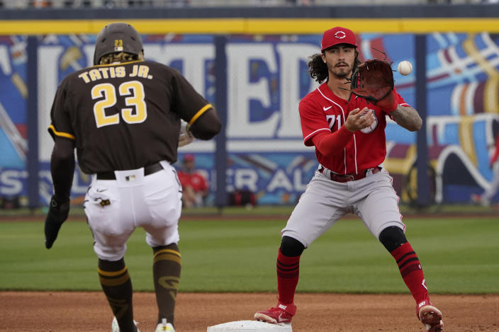 Cincinnati Reds second baseman Jonathan India, right, forces out San Diego Padres Fernando Tatis Jr. (23) on a ball hit by Manny Machado during the first inning of a spring training baseball game Tuesday, March 23, 2021, in Peoria, Ariz. (AP Photo/Sue Ogrocki)