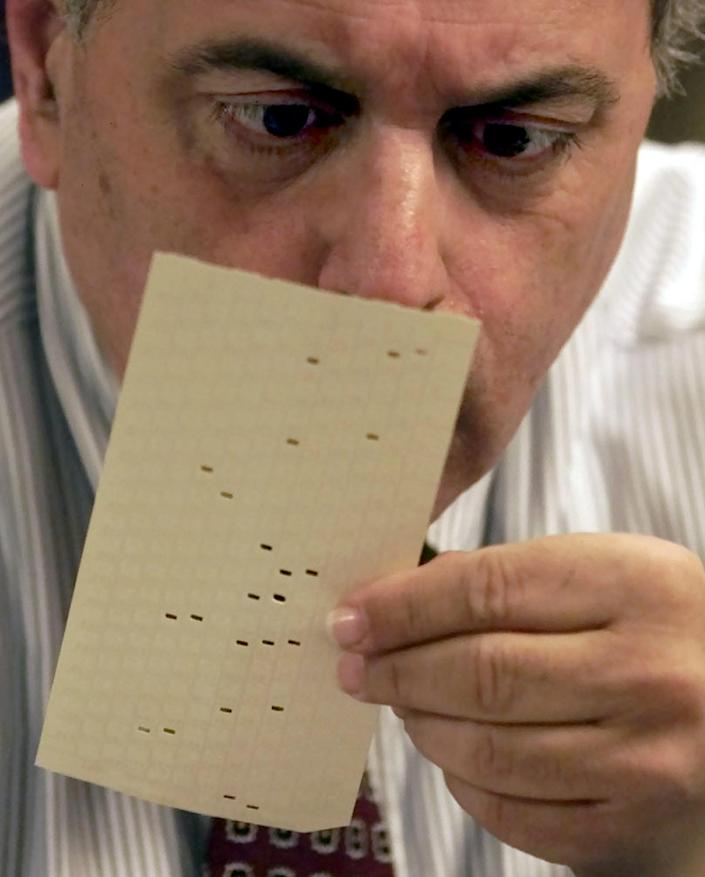 """FILE - In this Nov. 22, 2000 file photo, Broward County, Fla. canvassing board member Judge Robert Rosenberg examines a challenged vote at the Broward County Emergency Operations Center in Plantation, Fla. The mere mention of the 2000 election unsettles people in Palm Beach County. The county's poorly designed """"butterfly ballot"""" confused thousands of voters, arguably costing Democrat Al Gore the state, and thereby the presidency. Gore won the national popular vote by more than a half-million ballots. But George W. Bush became president after the Supreme Court decided, 5-4, to halt further Florida recounts, more than a month after Election Day. Bush carried the state by 537 votes, enough for an Electoral College edge, and the White House. (AP Photo/Wilfredo Lee, File)"""