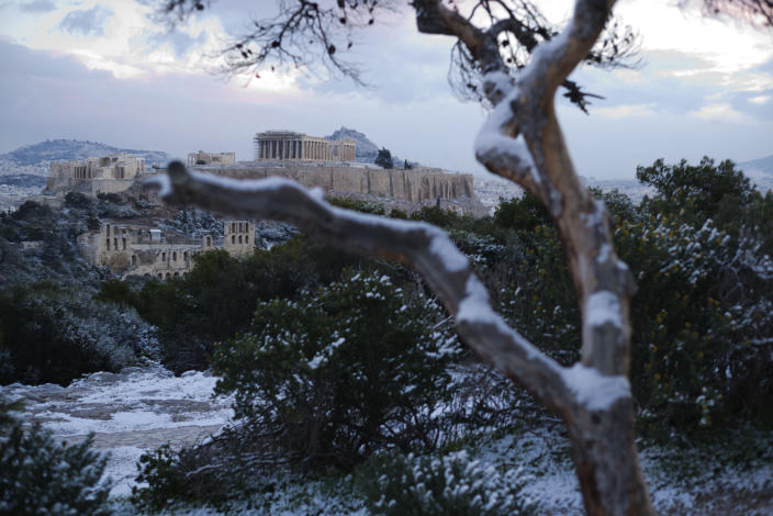 Snow covers a tree in front of the ancient Acropolis hill with the 500BC Parthenon temple, after snow fell in Athens, on Tuesday, Jan. 8, 2019. (AP Photo/Petros Giannakouris)