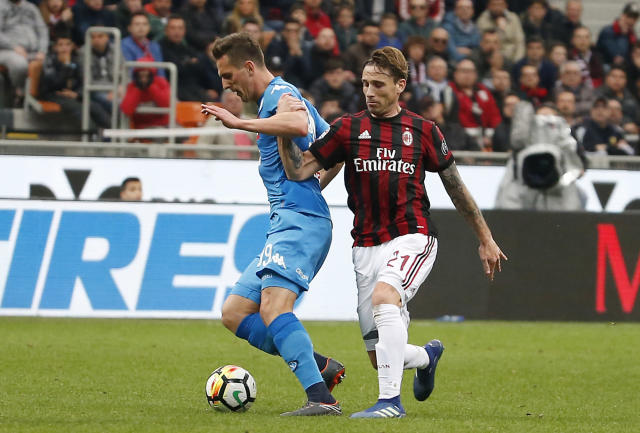 AC Milan's Lucas Biglia, right, challenges for the ball with Napoli's Arkadiusz Milik during the Serie A soccer match between AC Milan and Napoli at the San Siro stadium in Milan, Italy, Sunday, April 15, 2018. (AP Photo/Antonio Calanni)