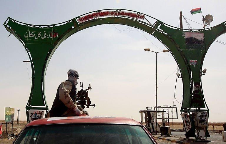 A Libyan rebel rides on the back of a truck in the eastern town of Ajdabiya. Libyan regime forces pounded rebels with heavy artillery west of Ajdabiya on Sunday, forcing hundreds of residents and some fighters to flee the key crossroads town, as a refugee rescue operation in Misrata was under way
