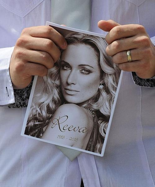 A relative of the late South African model Reeva Steenkamp holds the funeral program at the crematorium building in Port Elizabeth, South Africa on February 19, 2013. With the South African sporting hero already facing a tough fight to win bail, the prosecution presented police evidence to flesh out the charge he deliberately murdered the cover girl on Valentine's Day