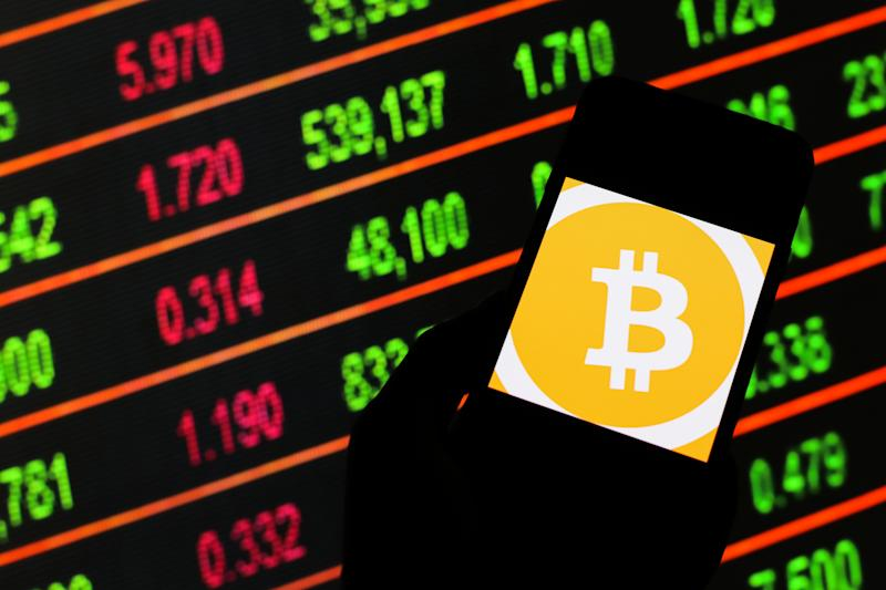 POLAND - 2020/03/13: In this photo illustration a Bitcoin cryptocurrency logo seen displayed on a smartphone. Stock market prices in the background as stock markets tumble all over the world. (Photo by Filip Radwanski/SOPA Images/LightRocket via Getty Images)