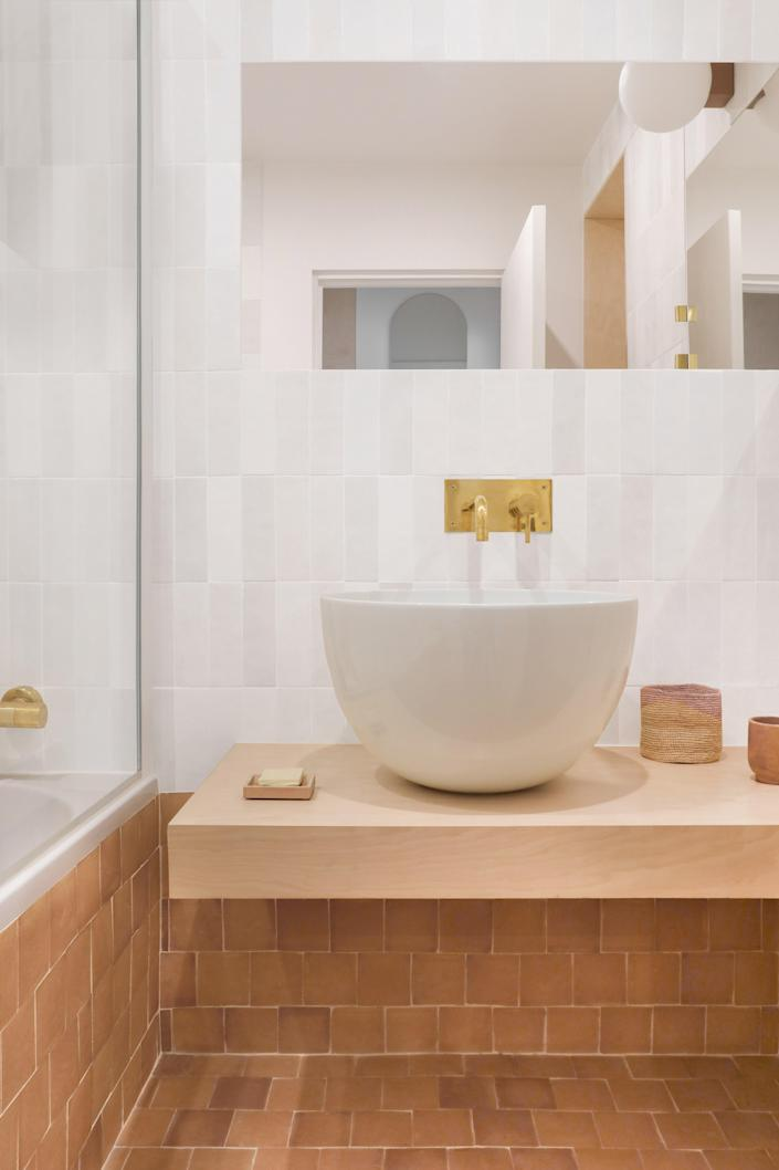 An &Tradition wall light was placed in the peaceful bathroom, where natural materials prevail.