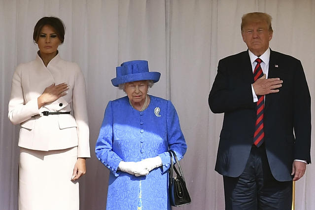 <p>Britain's Queen Elizabeth II, center, stands with President Donald Trump and first lady Melania on the dias in the Quadrangle as they listen to a band of guardsmen play the U.S. national anthem during a ceremonial welcome at Windsor Castle, Friday, July 13, 2018 in Windsor, England. (Photo: Ben Stansall/Pool Photo via AP) </p>