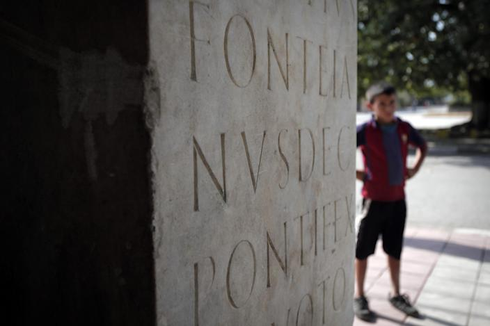 This Friday, Oct. 5, 2012 photo shows part of ancient Roman inscription on a column, found on the site of Ratiaria, an ancient Roman settlement located on the banks of the Danube, in the northwest corner of Bulgaria. Located on the crossroads of many ancient civilizations, Bulgarian scholars rank their country behind only Italy and Greece in Europe for the numbers of antiquities lying in its soil. But Bulgaria has been powerless to prevent the rape of its ancient sites, depriving the world of part of its cultural legacy and also costing this impoverished Balkan nation much-needed tourism revenue. (AP Photo/Valentina Petrova)