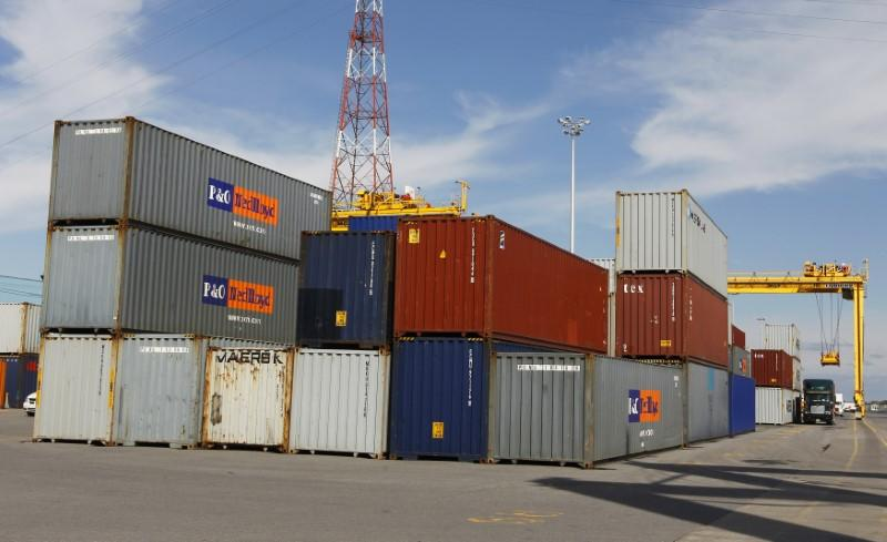 A truck is loaded with a container at the Port of Montreal