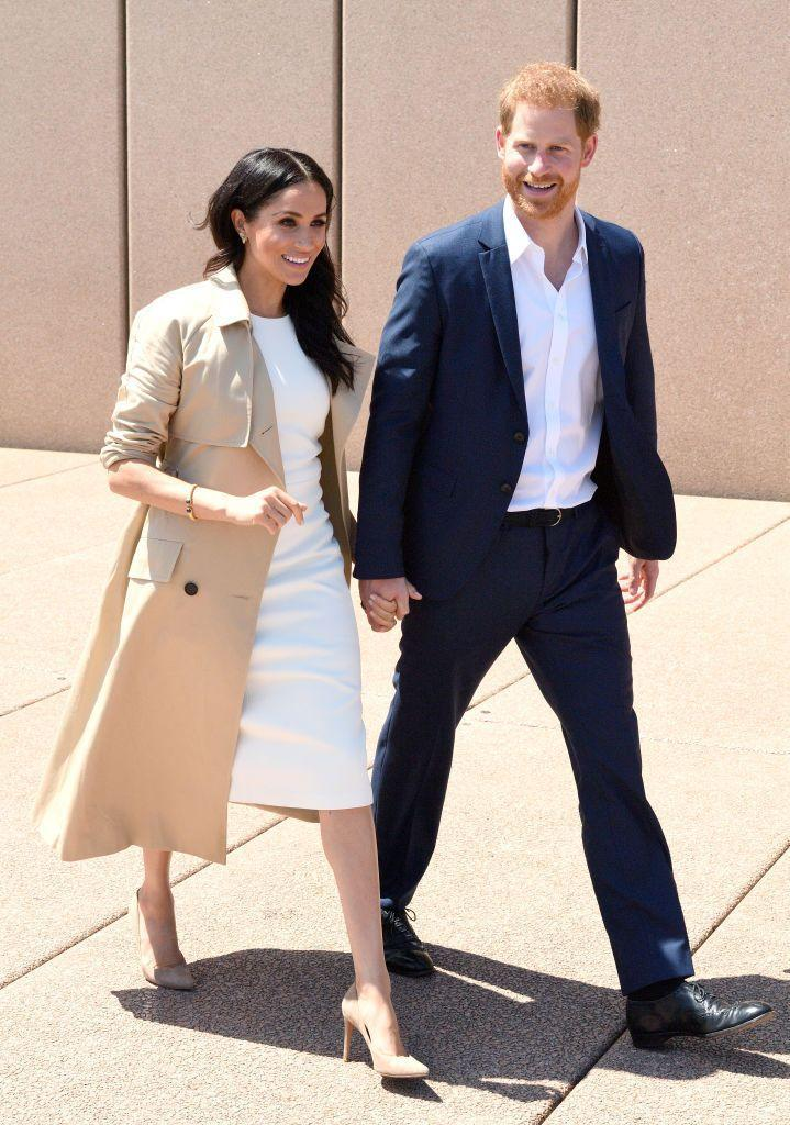 """<p>Prince Harry and Meghan Markle kicked off their royal tour with a <a href=""""https://www.townandcountrymag.com/society/tradition/g23796309/prince-harry-meghan-markle-royal-tour-australia-day-1-photos/"""" rel=""""nofollow noopener"""" target=""""_blank"""" data-ylk=""""slk:busy day in Sydney."""" class=""""link rapid-noclick-resp"""">busy day in Sydney. </a>The Duchess <a href=""""https://www.townandcountrymag.com/style/fashion-trends/a23797964/meghan-markle-white-karen-gee-dress-royal-tour-australia-day-1/"""" rel=""""nofollow noopener"""" target=""""_blank"""" data-ylk=""""slk:wore a white dress"""" class=""""link rapid-noclick-resp"""">wore a white dress </a>by Australian designer Karen Gee with nude heels. She completed the outfit with a trench coat by Martin Grant. Meghan paid tribute to Princess Diana with her jewelry choices for the day: she <a href=""""https://www.townandcountrymag.com/style/jewelry-and-watches/a23828704/meghan-markle-princess-diana-jewelry-earrings-bracelet-royal-tour/"""" rel=""""nofollow noopener"""" target=""""_blank"""" data-ylk=""""slk:wore Diana's earrings and bracelet"""" class=""""link rapid-noclick-resp"""">wore Diana's earrings and bracelet</a> as well.</p>"""