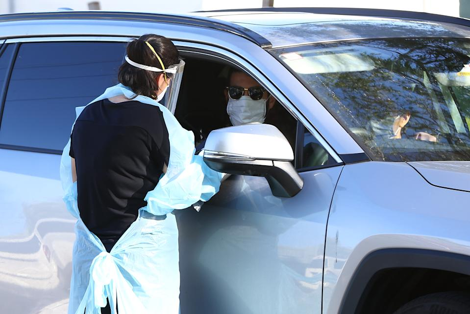 PERTH, AUSTRALIA - FEBRUARY 01: Members of the public attend the Rivervale drive thru Covid-19 testing clinic on February 01, 2021 in Perth, Australia. Lockdown restrictions are now in place across the Perth, Peel and South West regions of Western Australia following the discovery of a positive community COVID-19 case in a worker from a quarantine hotel facility.  As of 6pm on Sunday, people Perth, Peel and the South West are subject to stay at home orders, and will only be allowed to leave their homes to shop for essentials, for medical or health needs, exercise within their neighbourhood or travel to work if they cannot work from home. Face masks are now mandatory outdoors, with all restrictions to remain in place until 6pm on February 5. (Photo by Paul Kane/Getty Images)