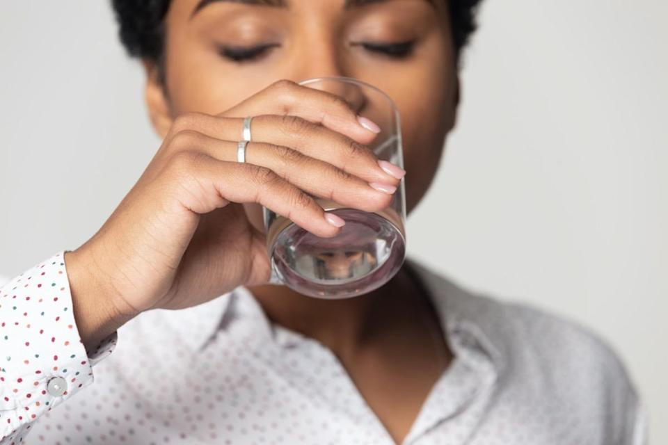 close up with closed eyes drinking clean mineral water, young woman holding glass