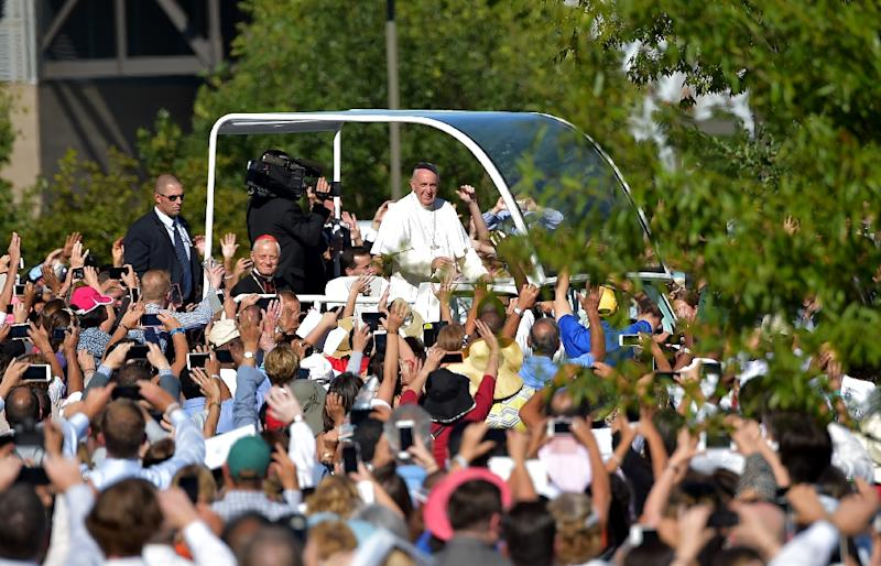 Thousands of people lined the streets for a brief glimpse of the 78-year-old Argentine pontiff, who stood, smiled and waved from his shiny white popemobile (AFP Photo/Vincenzo Pinto)