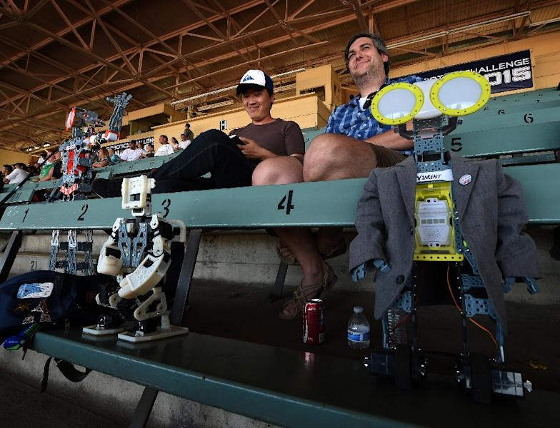 The robot named 'Meccano' (L) and others watch the action during the finals of the DARPA Robotics Challenge at the Fairplex complex in Pomona, California on June 6, 2015 (AFP Photo/Mark Ralston)