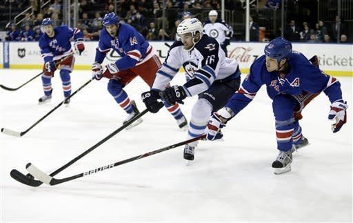 Winnipeg Jets' Andrew Ladd (16) and New York Rangers' Marc Staal (18) fight for control of the puck during the first period of an NHL hockey game Tuesday, Feb. 26, 2013, in New York. (AP Photo/Frank Franklin II)
