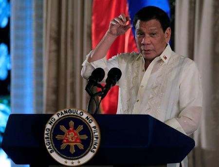 FILE PHOTO: Duterte gestures as he delivers his speech during the oath taking of PNP star rank officers in Manila