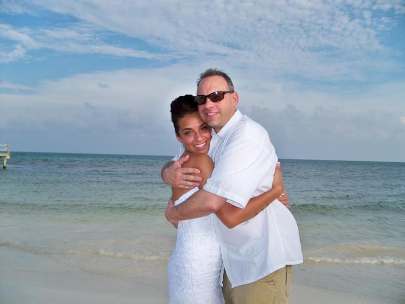 This May 13, 2013 image provided by Azia Wiscombe Ludwig shows Ludwig with her father, Clifford Robert Wiscombe II, shortly after her wedding in Playa del Carmen, Mexico. Ludwig's father died from a fall at a Mexican hotel, and Ludwig says the complicated logistics of repatriating his remains added to her grief and shock. Thousands of Americans die while traveling abroad each year _ including actor James Gandolfini, who died in Italy _ and the process of bringing their bodies home can include hassles ranging from bureaucratic hurdles to high fees. (AP Photo/Azia Wiscombe Ludwig)