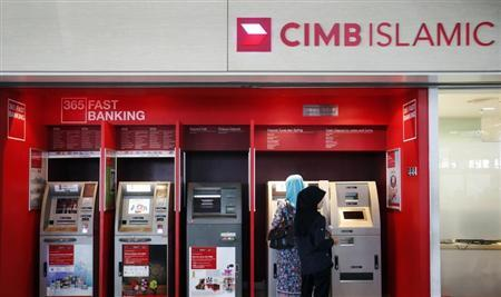 People withdraw cash from an ATM at a CIMB Islamic branch in Sepang outside Kuala Lumpur