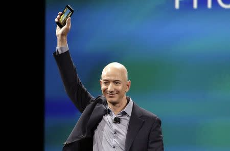 Amazon CEO Jeff Bezos shows off his company's new smartphone, the Fire Phone, at a news conference in Seattle, Washington June 18, 2014. REUTERS/Jason Redmond
