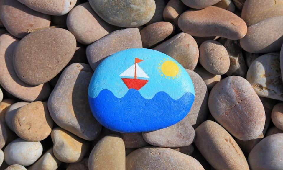 Red sailing boat painted on a pebble