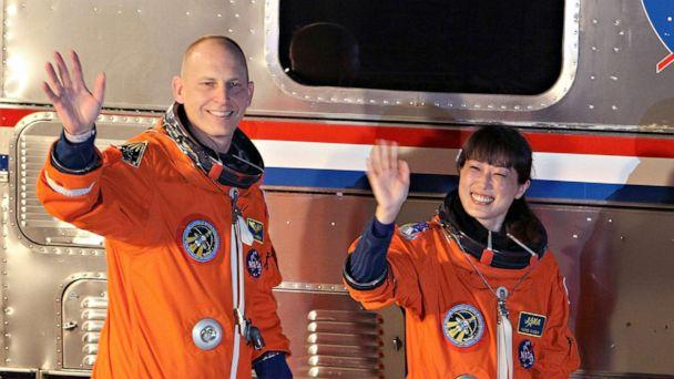 FILE PHOTO: NASA astronaut Clayton Anderson, left, and NASA's STS-131 Japan Aerospace Exploration Agency astronaut Naoko Yamazaki wave as they walk out of the operations and checkout building at Kennedy Space Center April 5, 2010 in Cape Canaveral, Fla. (Joe Raedle/Getty Images)
