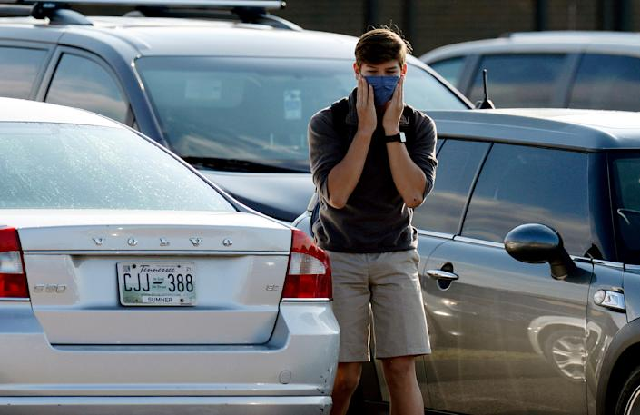 A Merrol Hyde Magnet School student adjusts his mask as he arrives for the first day of school on Aug. 3, 2020, in Hendersonville, Tenn. Sumner was the first school district in Middle Tennessee to go back to in-person classes during the COVID-19 pandemic.